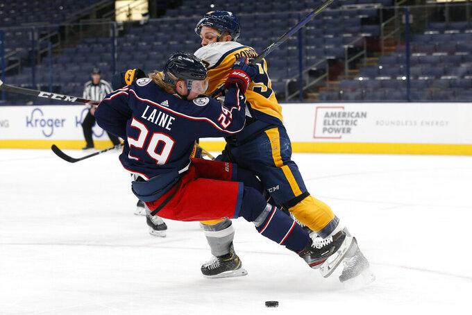 Nashville Predators' Mark Borowiecki, right, knocks Columbus Blue Jackets' Patrik Laine to the ice during the second period of an NHL hockey game Thursday, Feb. 18, 2021, in Columbus, Ohio. (AP Photo/Jay LaPrete)