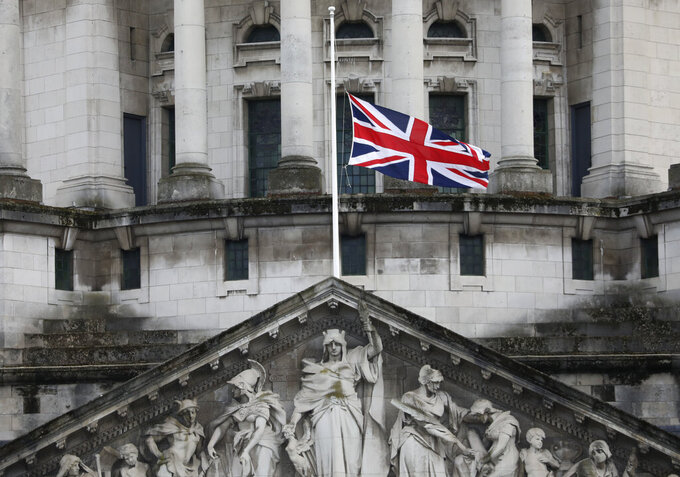 Flags fly at half-staff on City Hall in Belfast, Northern Ireland, Friday, April 9, 2021 in respect of Britain's Prince Philip who died earlier in the day. Prince Philip, the irascible and tough-minded husband of Queen Elizabeth II who spent more than seven decades supporting his wife in a role that both defined and constricted his life, has died, Buckingham Palace said Friday. He was 99. (AP Photo/Peter Morrison)