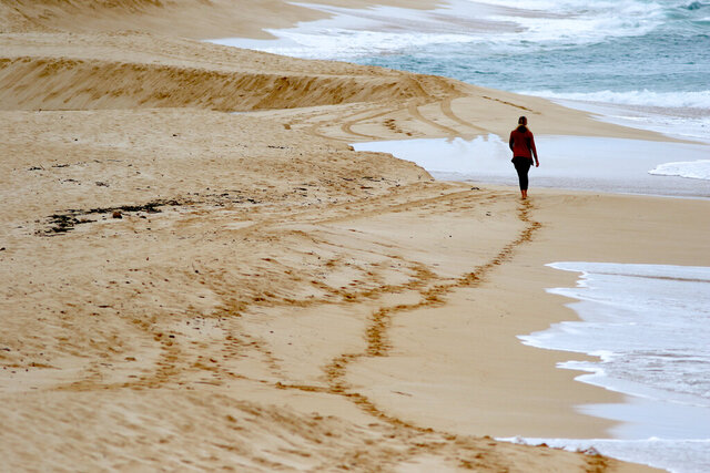 A woman walks on an empty beach on Oahu's North Shore near Haleiwa, Hawaii, Tuesday, March 31, 2020. Hawaii Gov. David Ige is further tightening travel restrictions to limit the spread of the coronavirus by ordering people moving between islands to adhere to a 14-day self-quarantine. The order takes effect at midnight on Wednesday. It won't apply to essential workers like health care workers traveling to other islands.The order comes a week after the governor ordered everyone arriving in the state from other states or overseas to follow the same two-week quarantine. He's also ordered everyone in the state to stay at home for the next month.(AP Photo/Caleb Jones)