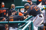Baltimore Orioles Anthony Santander (25) gives an elbow-bump to teammates in their dugout after coring a run during the first inning of a baseball game against the Washington Nationals in Washington, Friday, Aug. 7, 2020. (AP Photo/Manuel Balce Ceneta)