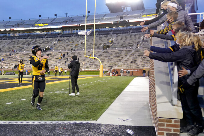 Missouri quarterback Connor Bazelak tosses a souvenir to fans as he heads off the field following a 20-10 victory over Kentucky in an NCAA college football game Saturday, Oct. 24, 2020, in Columbia, Mo. (AP Photo/L.G. Patterson)