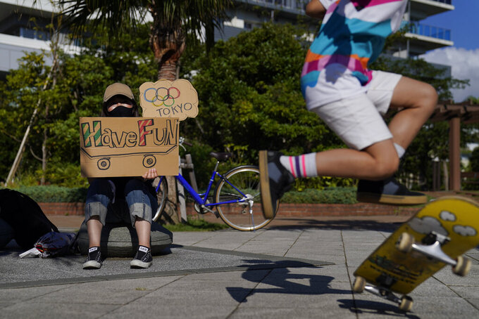Rie Nakamura, left, holds a sign to cheer for athletes arriving at the Ariake Urban Sports Park as her 8-year-old daughter, Ayane, practices a flip during the 2020 Summer Olympics, Sunday, July 25, 2021, in Tokyo. (AP Photo/Jae C. Hong)
