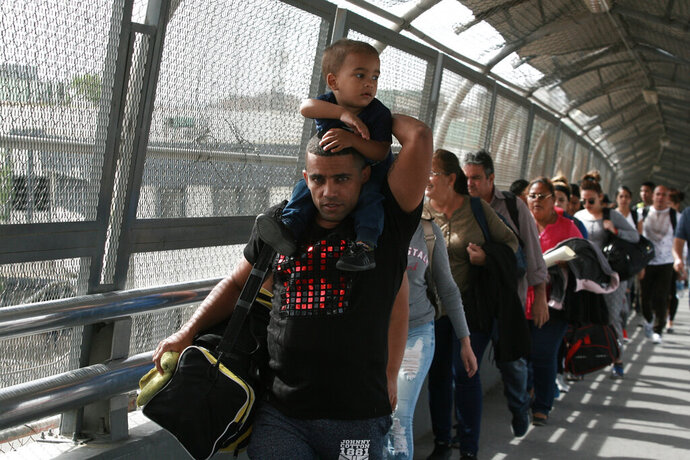 FILE - In this April 29, 2019 file photo, Cuban migrants are escorted by Mexican immigration officials in Ciudad Juarez, Mexico, as they cross the Paso del Norte International bridge to be processed as asylum seekers on the U.S. side of the border. Mexican Foreign Secretary Marcelo Ebrard said Thursday, Sept. 12, 2019 that Mexico's government doesn't agree with an