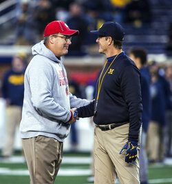 Wisconsin coach Paul Chryst, left, shakes hands with Michigan coach Jim Harbaugh on the Michigan Stadium field before an NCAA college football game in Ann Arbor, Mich., Saturday, Oct. 13, 2018. (AP Photo/Tony Ding)