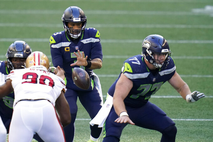 Seattle Seahawks quarterback Russell Wilson (3) takes a snap as center Ethan Pocic, right, blocks against the San Francisco 49ers during the first half of an NFL football game, Sunday, Nov. 1, 2020, in Seattle. (AP Photo/Elaine Thompson)