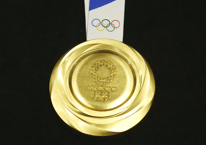 FILE - In this July 24, 2019, file photo, Tokyo 2020 Olympic gold medal is unveiled during a One Year to Go Olympic ceremony event in Tokyo. The Tokyo Olympics are about to open, and predicting the medal count will be more difficult than usual because of the pandemic and the absence of many qualifying events over the last year. (AP Photo/Koji Sasahara, File)