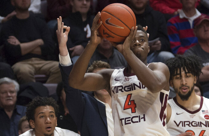 Virginia Tech guard Nahiem Alleyne (4) shoots from long range as someone signals a three pointer from the bench against North Carolina during the second half of an NCAA college basketball game in Blacksburg, Va., Wednesday, Jan. 22, 2020.(AP Photo/Lee Luther Jr.)