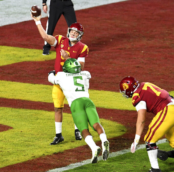 Oregon defensive end Kayvon Thibodeaux, 5,  pressures USC quarterback Kedon Slovis in the first half of an NCAA college football game at the Los Angeles Memorial Coliseum in Los Angeles on Friday, Dec. 18, 2020. (Keith Birmingham/The Orange County Register via AP)