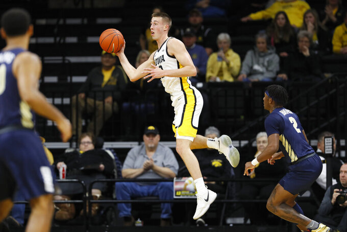 Iowa guard Joe Wieskamp, center, saves the ball in front of Oral Roberts guard Deondre Burns, right, during the first half of an NCAA college basketball game, Friday, Nov. 15, 2019, in Iowa City, Iowa. (AP Photo/Charlie Neibergall)