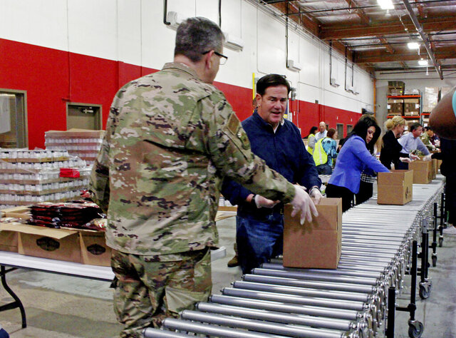 Arizona National Guard commander Major Gen. Michael McGuire, Gov. Doug Ducey, center, and Secretary of State Kimberly Yee pack food boxes at St. Mary's Food Bank in Phoenix Friday, March 20, 2020. The governor called out the Guard to help grocery stores restock shelves and went to the food bank to highlight shortages of donations and volunteers for charity operations triggered by the coronavirus outbreak. (AP Photo/Bob Christie)