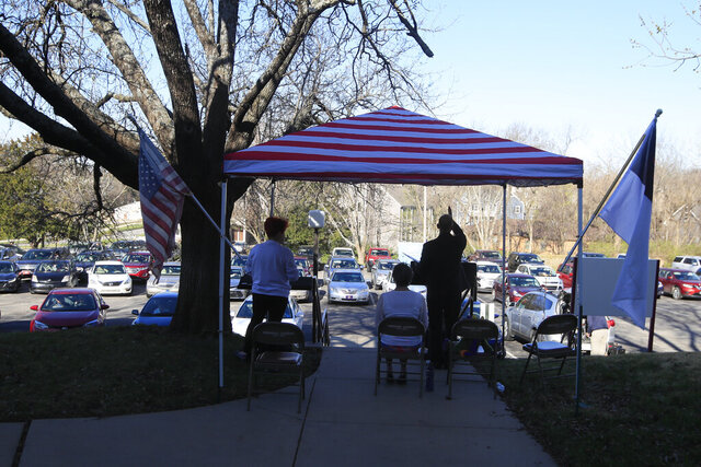 Pastor Lee leads a parking lot service at the Immanuel Lutheran Church In Lawrence, Kan., Sunday, March 29, 2020. The church plans two