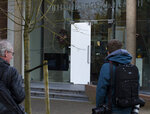 Journalists look at the damaged glass door of the Singer Museum in Laren, Netherlands, Monday March 30, 2020, where a Van Gogh painting was stolen. The Dutch museum that is currently closed to prevent the spread of the coronavirus says a painting by the Dutch master titled