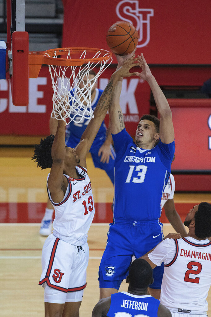 St. John's forward Isaih Moore, left, blocks Creighton forward Christian Bishop in the first half of an NCAA college basketball game Thursday, Dec. 17, 2020, in New York. (AP Photo/Kevin Hagen)