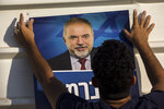 Israeli supporter of the leader of the Yisrael Beiteinu (Israel Our Home) right-wing nationalist party Avigdor Liberman hangs election poster outside the polling station, in the settlement of Nokdim, West Bank, Tuesday, Sept. 17, 2019. (AP Photo/Tsafrir Abayov)