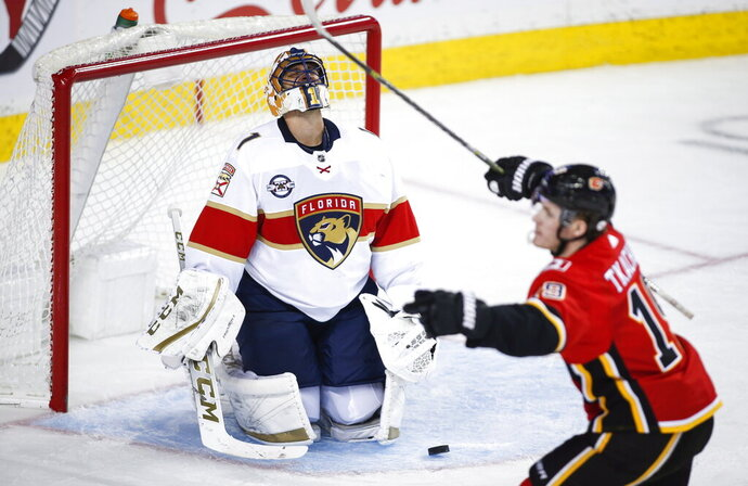 Florida Panthers goalie Roberto Luongo, left, reacts as Calgary Flames' Matthew Tkachuk celebrates his goal during third-period NHL hockey game action in Calgary, Alberta, Friday, Jan. 11, 2019. (Jeff McIntosh/The Canadian Press via AP)