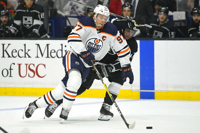 Edmonton Oilers center Connor McDavid, left, moves the puck while under pressure from Los Angeles Kings center Anze Kopitar during the first period of an NHL hockey game Sunday, Feb. 23, 2020, in Los Angeles. (AP Photo/Mark J. Terrill)