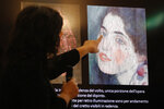 Italian art restorer Anna Selleri points at a slide showing a detail of a painting which was found last December near an art gallery and believed to be the missing Gustav Klimt's painting 'Portrait of a Lady' during a press conference in Piacenza, Italy, Friday, Jan. 17, 2020. Art experts have confirmed that a stolen painting discovered hidden inside an Italian art gallery's walls is Gustav Klimt's