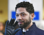 FILE - In this March 26, 2019, file photo, actor Jussie Smollett smiles and waves to supporters before leaving Cook County Court after his charges were dropped in Chicago. Text messages show the Chicago prosecutor whose office handled the case of