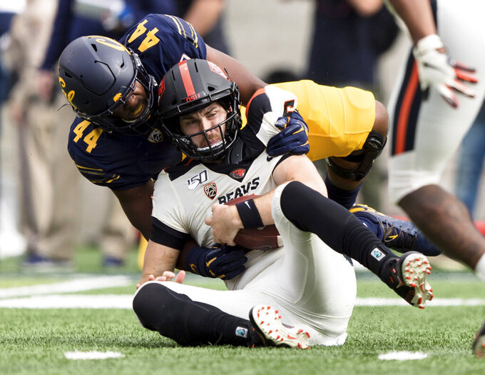 Oregon State quarterback Jake Luton, front, is sacked by California defensive end Zeandae Johnson in the first quarter of an NCAA college football game in Berkeley, Calif., Saturday, Oct. 19, 2019. (AP Photo/John Hefti)