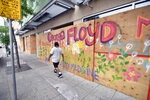 A pedestrian passes a colorful painted tribute to George Floyd on a boarded-up business, Thursday, June 18, 2020 in Minneapolis. Scores of businesses along Lake Street remain boarded up following riots, fires and looting. Floyd died in police custody after video shared online by a bystander showed former officer Derek Chauvin kneeling on Floyds' neck during his arrest as he pleaded that he couldn't breathe. (AP Photo/Jim Mone)