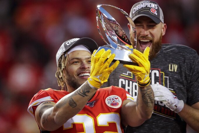Kansas City Chiefs' Tyrann Mathieu and Travis Kelce hold up the Lamar Hunt Trophy after the NFL AFC Championship football game against the Tennessee Titans Sunday, Jan. 19, 2020, in Kansas City, MO. The Chiefs won 35-24 to advance to Super Bowl 54. (AP Photo/Charlie Riedel)