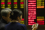 Investors monitor stock prices at a brokerage in Beijing on Thursday, Dec. 12, 2019. Asian shares are mixed after a wobbly day on Wall Street following the Federal Reserve announcement that it would leave interest rates unchanged. Japan's benchmark Nikkei 225, South Korea's Kospi and Hong Kong's Hang Seng rose in early Thursday trading. (AP Photo/Ng Han Guan)