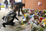 Mourners place flowers on a memorial outside the Davis Police Department for slain Davis Police Officer Natalie Corona, Friday, Jan. 11, 2019, in Davis, Calif. Corona, 22, who had been on the job only a few weeks was shot and killed, Thursday, by a suspect who opened fire as she was investigating a three-car crash. The suspect was later found dead from a self-inflicted gunshot, following a standoff with officers. (AP Photo/Rich Pedroncelli)