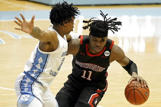 North Carolina guard Caleb Love, left, guards Northeastern guard Jahmyl Telfort (11) during the second half of an NCAA college basketball game in Chapel Hill, N.C., Wednesday, Feb. 17, 2021. (AP Photo/Gerry Broome)