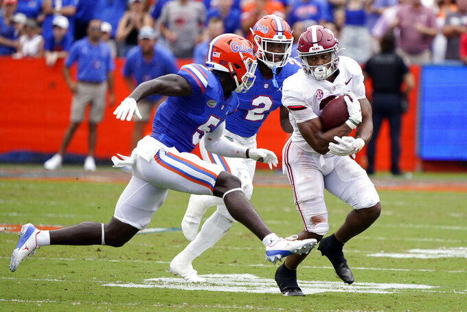 Alabama running back Jase McClellan, right, gains yardage as he tries to get past Florida cornerback Kaiir Elam (5) and linebacker Amari Burney (2) during the first half of an NCAA college football game, Saturday, Sept. 18, 2021, in Gainesville, Fla. (AP Photo/John Raoux)
