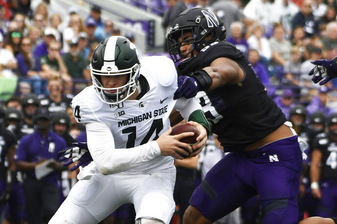 Michigan State quarterback Brian Lewerke (14) runs the ball as Northwestern defensive lineman Eku Leota (53) tries to tackle him during the first half of an NCAA college football game, Saturday, Sept. 21, 2019, in Evanston, Ill. (AP Photo/David Banks)