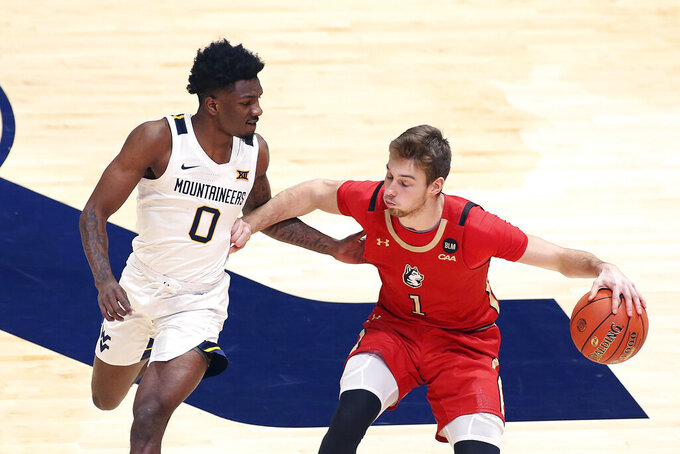Northeastern guard Vito Cubrilo (1) is defended by West Virginia guard Kedrian Johnson (0) during the second half of an NCAA college basketball game Tuesday, Dec. 29, 2020, in Morgantown, W.Va. (AP Photo/Kathleen Batten)