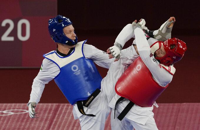 Maksim Khramtsov of the Russian Olympic Committee, left, attacks Jordan's Saleh Al-Sharabaty during the taekwondo men's 80kg match at the 2020 Summer Olympics, Monday, July 26, 2021, in Tokyo, Japan. (AP Photo/Themba Hadebe)