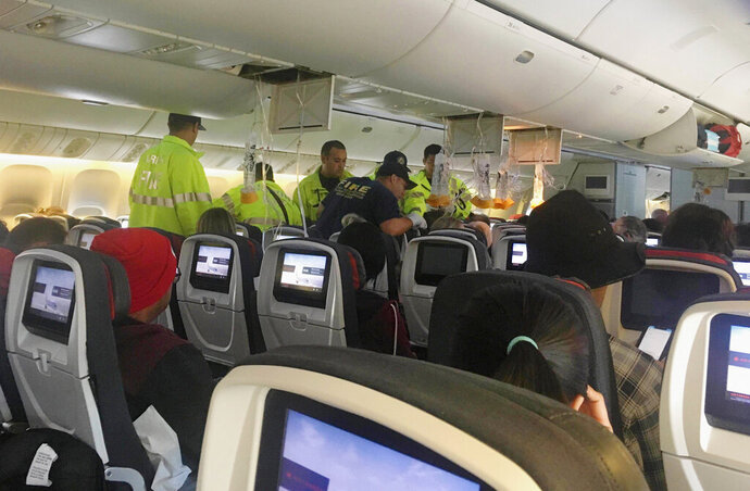 FILE - In this Thursday, July 11, 2019 photo provided by Tim Tricky of the band Hurricane Fall, emergency workers treat a passenger on an Air Canada flight to Australia that was diverted and landed at Daniel K. Inouye International Airport in Honolulu. The flight from Vancouver to Sydney encountered