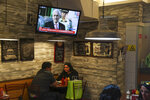 A TV screen shows a live broadcast of Chilean President Sebastian Pinera at a restaurant in Santiago, Chile, Wednesday, Oct. 30, 2019. Chilean President Sebastian Pinera cancelled two major international summits after nearly two weeks of nationwide protests over economic inequality that have left at least 20 dead and damaged businesses and infrastructure around the country. (AP Photo/Esteban Felix)
