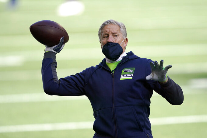 Seattle Seahawks head coach Pete Carroll tosses a football before an NFL wild-card playoff football game against the Los Angeles Rams, Saturday, Jan. 9, 2021, in Seattle. (AP Photo/Ted S. Warren)
