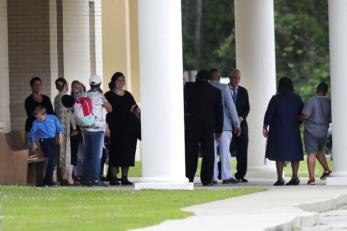 FILE - In this March 29, 2020, file photo, congregants gather after services at the Life Tabernacle Church in Central, La. Pastor Tony Spell has defied a shelter-in-place order by Louisiana Gov. John Bel Edwards, due to the new coronavirus pandemic, and continues to hold church services with hundreds of congregants. (AP Photo/Gerald Herbert, File)