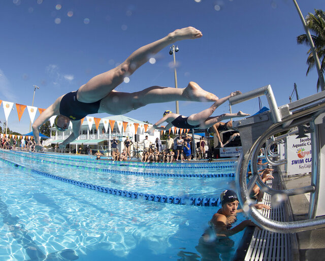In this photo provided by the Florida Keys News Bureau, from left, University of Michigan swimmers Caroline Sisson and Miranda Tucker leap off the starting blocks during the Orange Bowl Swim Classic Friday, Jan. 3, 2020, in Key Largo, Fla. The Wolverines took top honors in the women's division, while the University of Wisconsin - La Crosse won the men's division.  (Stephen Frink/Florida Keys News Bureau via AP)