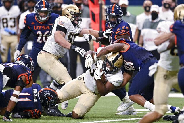 Army's Jakobi Buchanan, center, is brought down by UTSA's Jamal Ligon (88) during an NCAA college football game on Saturday, Oct. 17, 2020, in San Antonio, Texas. (AP Photo/Darren Abate)