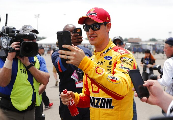 Joey Logano goes live on his cellphone after the pole presentation for the NASCAR cup series race at Michigan International Speedway, Saturday, June 8, 2019, in Brooklyn, Mich. (AP Photo/Carlos Osorio)