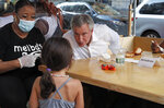 Four-year-old Olivia Rigie, center, thanks New York City Mayor Bill de Blasio for reopening the city's playgrounds, as he dined with his wife, not seen, and restaurant owner Melba Wilson in a private outdoor booth at Melba's in Harlem on the first day of the current phase of the reopening of the city during the coronavirus outbreak, Monday, June 22, 2020, in New York. Restaurants, hair and nail salons, barber shops, playgrounds and some retail outlets were allowed to reopen to the public. Olivia's parents were seated nearby. (AP Photo/Kathy Willens)