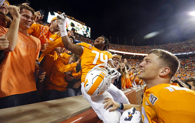 Tennessee offensive lineman K'Rojhn Calbert (74) and quarterback Brian Maurer (18) celebrate with fans after their 41-21 win over South Carolina in an NCAA college football game Saturday, Oct. 26, 2019, in Knoxville, Tenn. (AP Photo/Wade Payne)