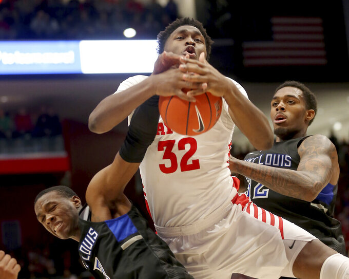 Dayton's Jordy Tshimanga (32) battles St. Louis 's Javonte Perkins (3) and Jimmy Bell Jr, right, for a rebound during the second half of an NCAA college basketball game, Saturday, Saturday, Feb. 1, 2020, in Dayton, Ohio. (AP Photo/Tony Tribble)