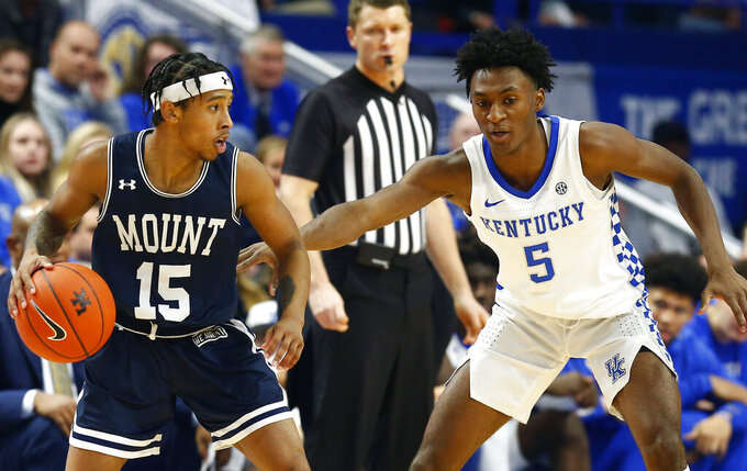 Mount St. Mary's Damian Chong Qui (15) is guarded by Kentucky's Immanuel Quickley (5) during the first half of an NCAA college basketball game in Lexington, Ky., Friday, Nov. 22, 2019. (AP Photo/James Crisp)