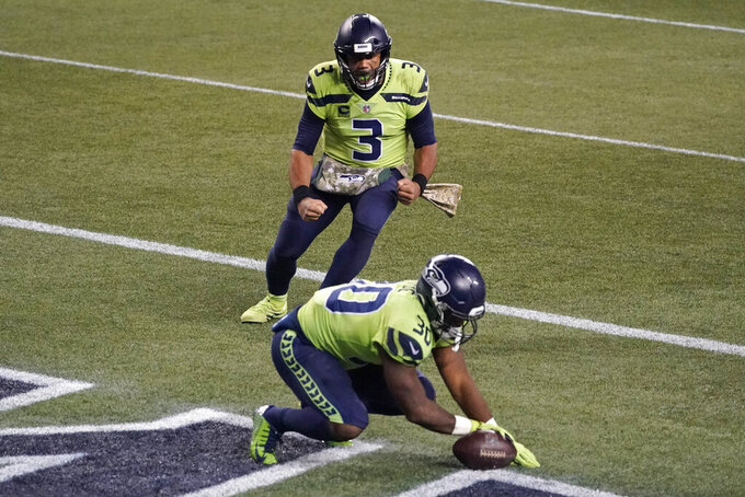 Seattle Seahawks quarterback Russell Wilson (3) reacts after running back Carlos Hyde (30) score a touchdown during the second half of an NFL football game against the Arizona Cardinals, Thursday, Nov. 19, 2020, in Seattle. (AP Photo/Elaine Thompson)