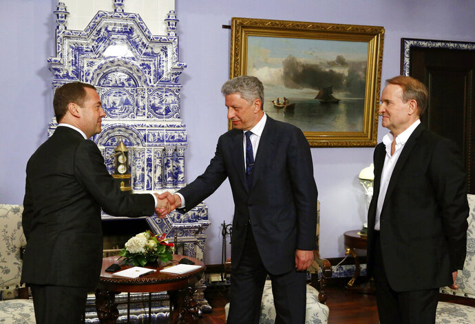 Russian Prime Minister Dmitry Medvedev, left, shakes hands with Ukrainian presidential candidate Yuri Boyko, center, as Ukrainian politician Viktor Medvedchuk, right, attends their meeting in Moscow, Russia, Friday, March 22, 2019. A Ukrainian presidential candidate has traveled to Moscow to meet with the Russian prime minister to discuss gas supplies. (Yekaterina Shtukina, Sputnik, Government Pool Photo via AP)
