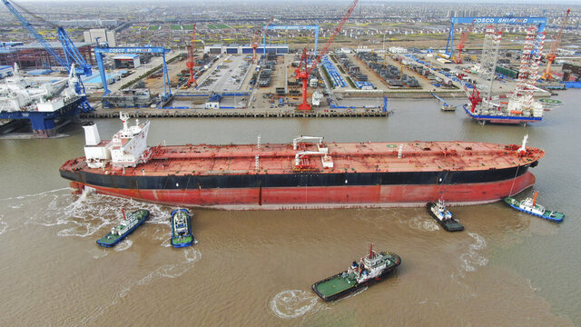 FILE - In this photo taken Monday, March 16, 2020, tugboats push a 300,000-ton very large crude carrier (VLCC) to a shipyard on the Yangtze River for retrofit in Qidong city in east China's Jiangsu province China. China, the world's biggest energy consumer, is taking advantage of a plunge in global oil prices due to the coronavirus outbreak to build up its stockpiles of crude. Imports rose 4.5% in March over a year earlier even as the world's second-largest economy shut down to fight the virus and demand collapsed. (Chinatopix Via AP, File)