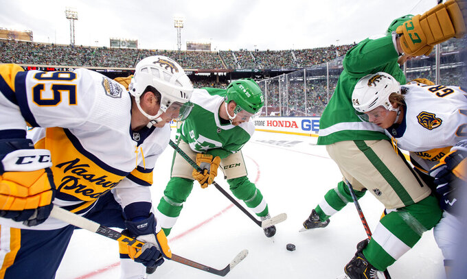 Nashville Predators' centers Matt Duchene (95) and Mikael Granlund (64) battle for the puck with Dallas Stars center Radek Faksa (12) and defenseman Jamie Oleksiak, right, in the first period of the NHL Winter Classic hockey game at the Cotton Bowl, Wednesday, Jan. 1, 2020, in Dallas. (AP Photo/Jeffrey McWhorter)