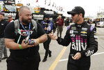 Jimmie Johnson, right, hands a pen back to a fan after signing an autograph before a NASCAR auto race practice at Daytona International Speedway, Saturday, Feb. 9, 2019, in Daytona Beach, Fla. (AP Photo/John Raoux)