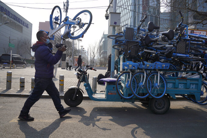 A worker collects bicycles from a bike-sharing service in Beijing Thursday, Feb. 25, 2021. The state of the world's second largest economy takes precedence among the myriad issues presented by Chinese Premier Li Keqiang in his address at the National People's Congress opening session to take place on Friday, March 5. 2021. (AP Photo/Ng Han Guan)