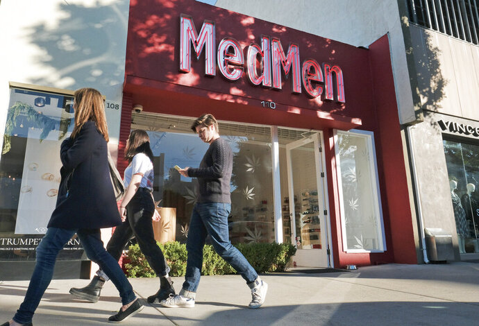 FILE - This Thursday, Dec. 21, 2017 file photo shows the MedMen marijuana dispensary in Los Angeles. Marijuana stocks have come down hard from their highs a year ago, and the skid isn't just spooking investors. On Tuesday, Oct. 8, 2019, MedMen Enterprises Inc., which sells legal cannabis in California and 11 other states, backed out of a blockbuster deal to buy PharmaCann, a Chicago-based marijuana company with operations in eight states. (AP Photo/Richard Vogel, File)